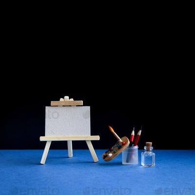 Wooden easel with textured blank paper canvas on blue black background