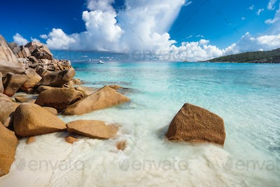 Stones on tropical sandy beach with crystal clear blue ocean bay at La Digue Island, Seychelles