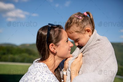 Mother drying daughter with towwl outdoors after swimming