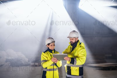 Engineers standing outdoors on construction site, holding tablet