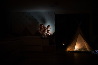 Family with children sitting indoors in bedroom, using laptop