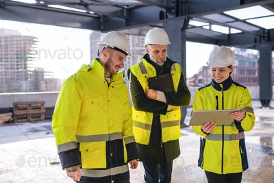 Group of engineers standing outdoors on construction site, using tablet