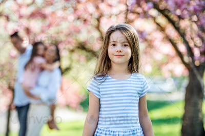 A small girl with family outside in spring nature, looking at camera