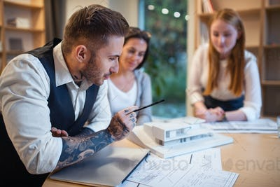Group of architects with model of house sitting indoors in office, working