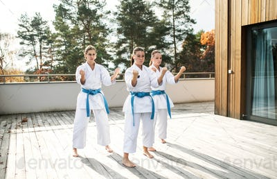 Group of young women practising karate outdoors on terrace