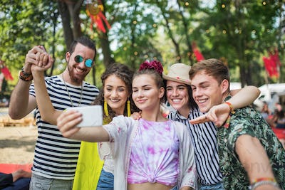 Group of young people at summer festival, taking selfie with smartphone