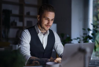 A businessman with laptop sitting at the desk indoors in office, working late