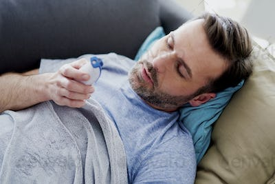 Ill man with high temperature staying in bed