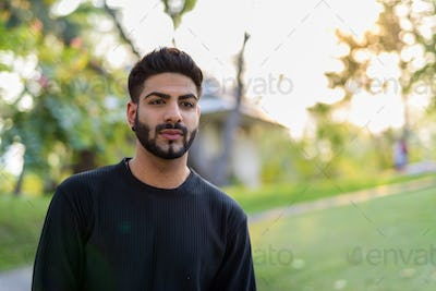 Young handsome Indian man at park