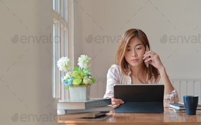 Female college student studying online at home is using a smartphone for advice from an instructor.