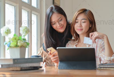Two teenage girls are shopping online with a tablet at home to order and pay online by credit card.