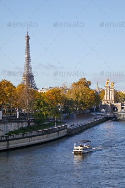 Seine river view with boat, Eiffel tower and Alexander III bridge in a sunny autumn day in Paris