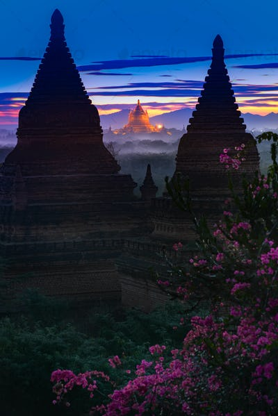 Shwezigon Pagoda Bagan Myanmar framed by Bell-shaped pagodas after sunset