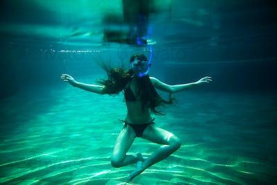 woman swim underwater pool with snorkel