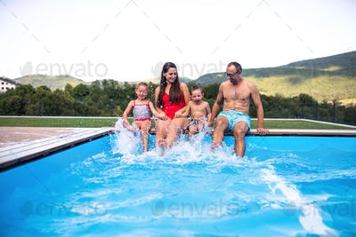 Young family with two small children sitting by swimming pool outdoors.