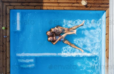 Top view of father with small children sitting in swimming pool outdoors.