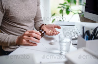 A businessman at the desk indoors in office, taking medicine pills, midsection.