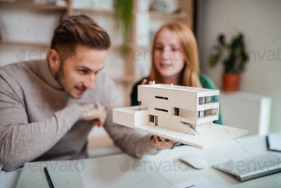 Architects with model of house sitting at the desk indoors in office, working.