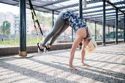 A young sportswoman doing exercise with TRX fitness straps outdoors.
