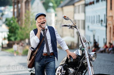 A senior businessman with motorbike in town, using smartphone.