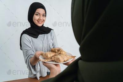 hijab woman and friend having ketupat together