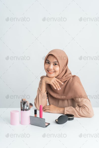woman smiling while sitting after do some make up