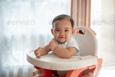 baby feeding time sitting on highchair