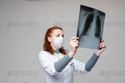 Lovely woman doctor in white medical clothes, mask, looks at lung snapshot, picture isolated on