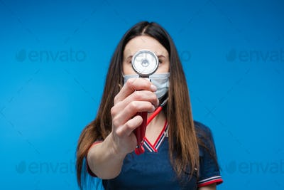 Beautiful woman doctor in white medical clothes, mask holds a phonendoscope, picture isolated on