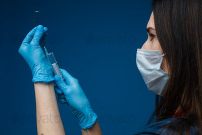 Doctor filling syringe with vaccine. COVID-19