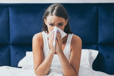 Sick Girl Blowing Nose In Tissue Sitting In Bed Indoor