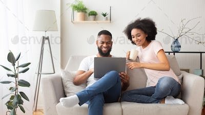 African american couple on couch with laptop
