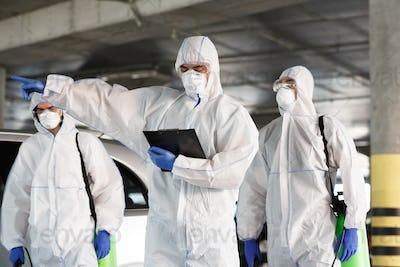 Men in virus protective suits enclosing the quarantine zone