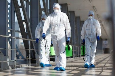 People in virus protective suits and mask disinfecting buildings