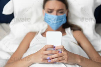Girl In Mask Using Smartphone Lying In Bed At Home