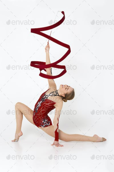 Gymnastic championship. Professional sportswoman in leotard practicing for competition on white