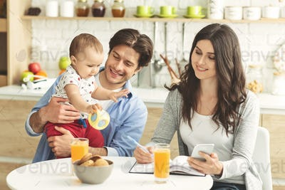 Young woman working at kitchen, spending morning with family