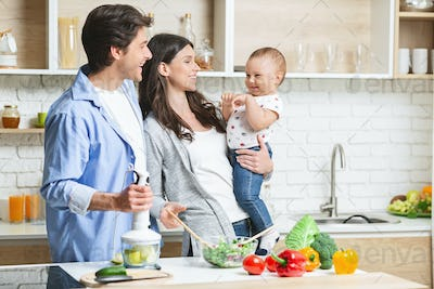 Happy family of three cooking together at kitchen