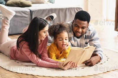 International family reading book on the floor