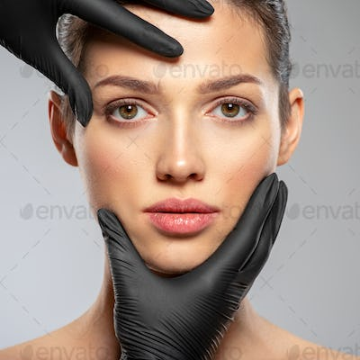 Plastic surgery doctor is touching face of a patient by hands.