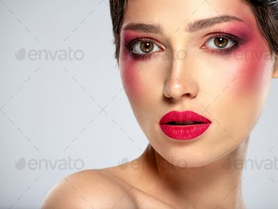 Beautiful brunette girl with bright eye makeup.