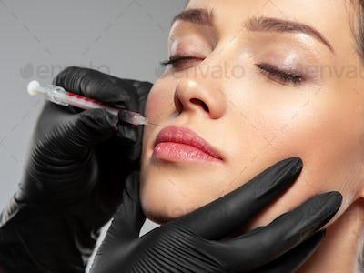 Caucasian woman getting botox cosmetic injection in the lips. Woman gets botox injection in her face