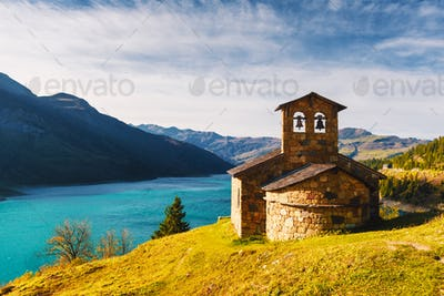Sunny picturesque view of stone chapel on Roselend lake