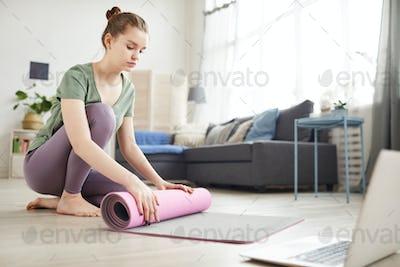 Woman preparing for yoga at home