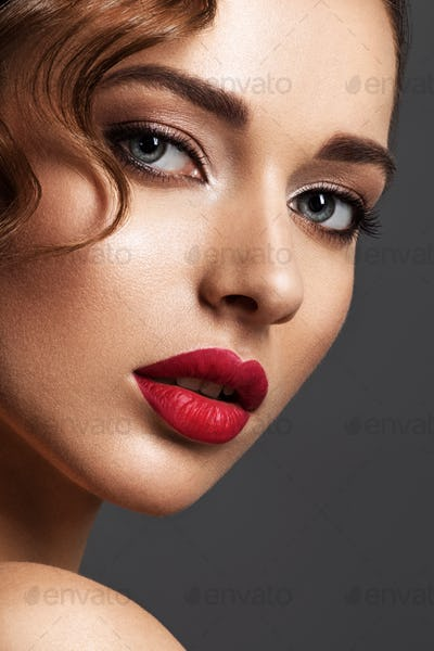 Beautiful face of young woman with red lipstick.