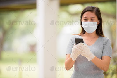 Young Asian woman using phone with mask and gloves