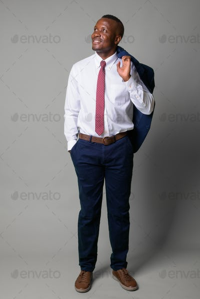 Full body shot of young happy African businessman against white background
