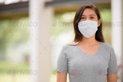 Young Asian woman wearing mask for protection from corona virus outbreak outdoors
