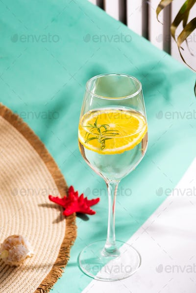 Creative summer backdrop from wide-brimmed hat and glass of refreshing cold citrus cocktail on a