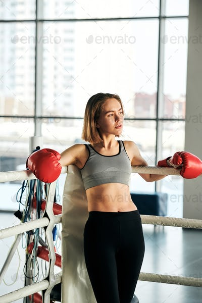 Young active female in red boxing gloves, grey crop top and black leggins